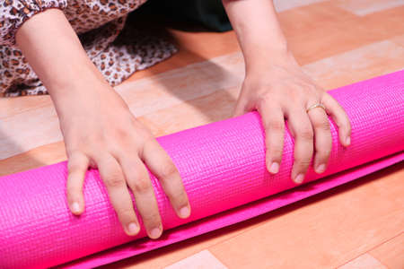 woman rolling exercise mat in living room.