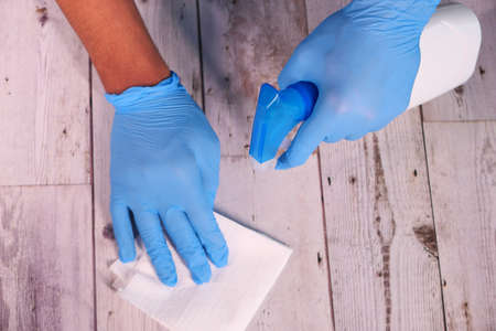 hand in blue rubber gloves holding spray bottle and wiping flat surface