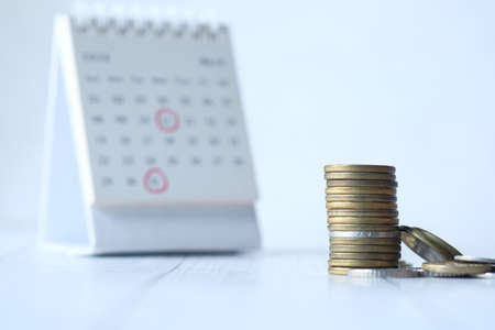 deadline concept with stack of coins and calendar on white background