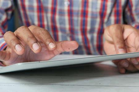 mans hand working on digital tablet on office desk