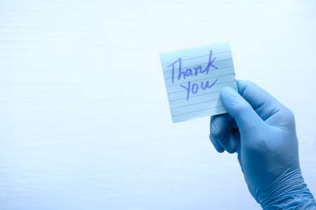 person hand in protective gloves holding thank you letter 版權商用圖片