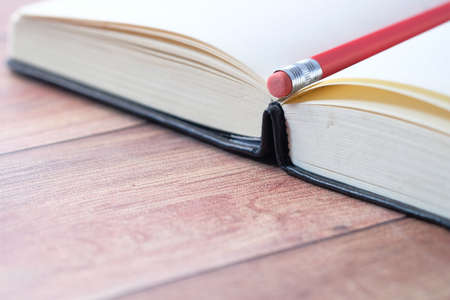 open book and a pencil on wooden table