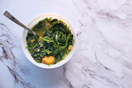 Top view of bowl with cooked spinach on table