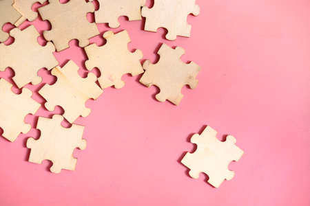 Jigsaw puzzle on pink background, top view .