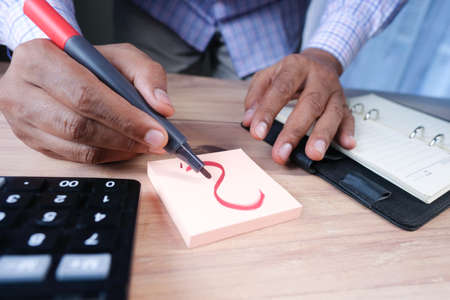 person hand drawing question mark on paper on office desk