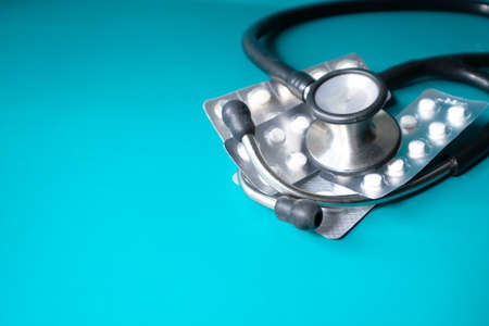blister pack and stethoscope on green background
