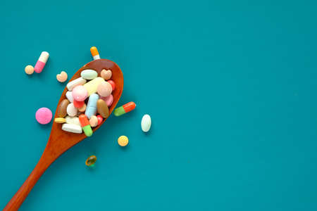 close up of colorful pills spilling on spoon on green background