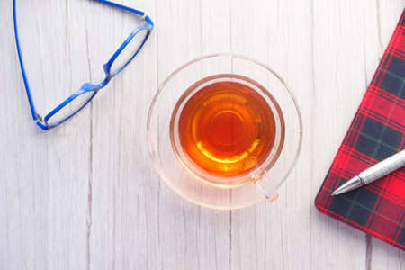 high angle view of tea, notepad and eyeglass on table 版權商用圖片