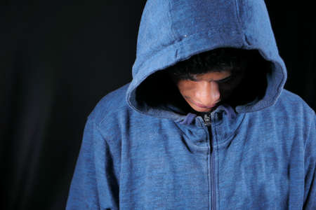 sad man in hood looking down isolated on black Stock Photo