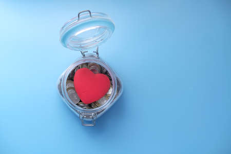 Red heart and coins in a jar on blue background Banque d'images
