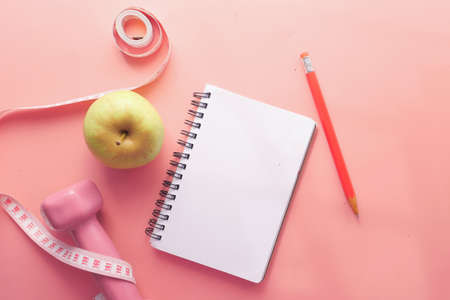 Fitness concept with dumbbell apple and notepad on pink Banque d'images