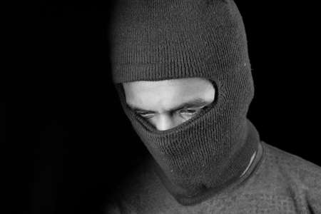 Thief in a mask on black background close up, Banque d'images