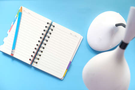 high angle view of open notepad and table lamp on blue background Banque d'images