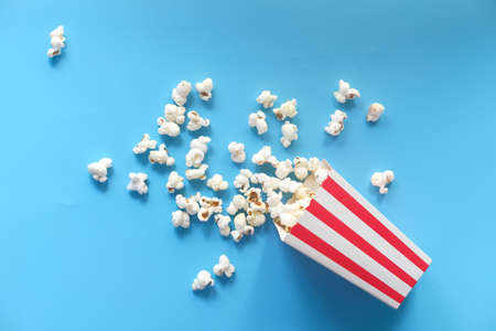 popcorn spilling from a container on blue background