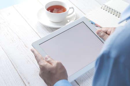 rear view of businessman using digital tablet on office desk