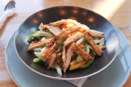 Grilled chicken and fresh vegetable salad on table.