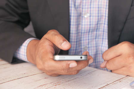 man in suit using smart phone on office desk Banque d'images