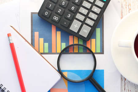 financial graph, magnifying glass and notepad on table Banque d'images
