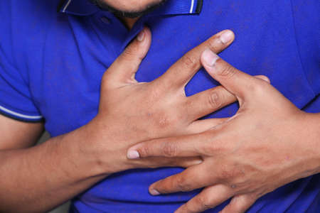 young man suffering pain in heart and holding chest with hand