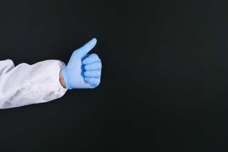 hand in medical gloves showing a thumb-up on black background Banque d'images