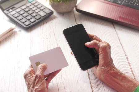 senior women hand holding credit card and using smart phone shopping online Banque d'images