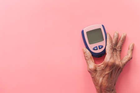 senior women holding diabetic measurement tools on pink Banque d'images