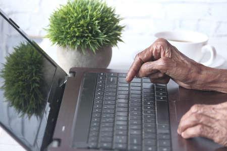 senior womens hand typing on laptop.