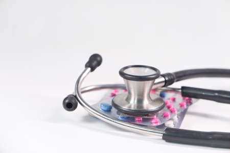Close up of stethoscope and blister packs on white background Stock fotó