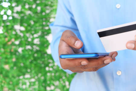 Man hand holding credit card and using smart phone shopping online