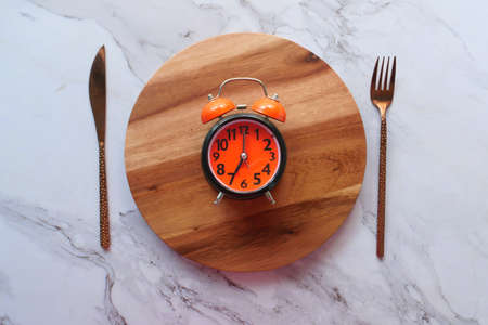 Alarm clock on plate on wooden table, top view.