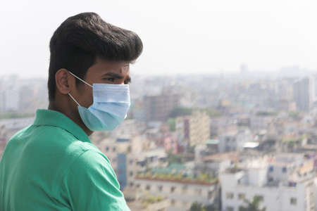 young man with protective face mask at city