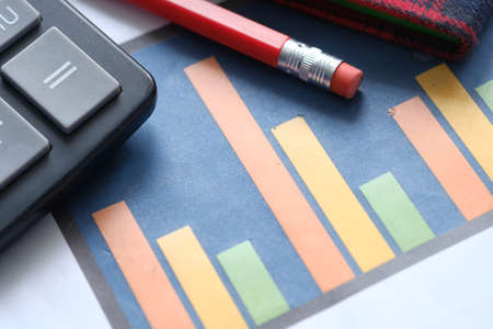 financial graph, calculator and notepad on table