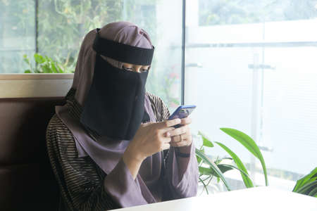Muslim women with head scarf using smart phone indoor
