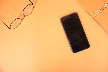 top view of smart phone and notepad on orange background