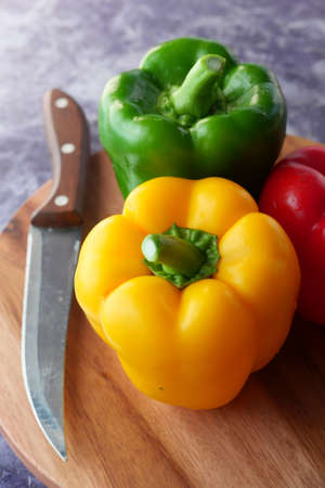 Yellow, green and red capsicum on wooden background