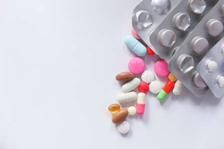 close up of colorful pills spilling on white background Stock fotó