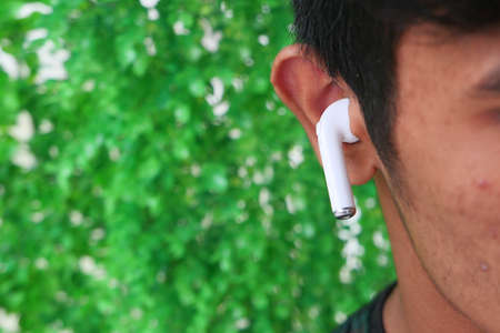 young man putting wireless hear phone close up Stock fotó