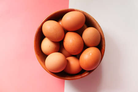 Top view of eggs in a bowl on color background Stock fotó