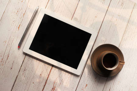Flat composition of digital tablet and tea on wooden background