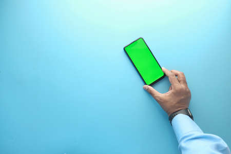 top view of hand holding smart phone on blue background