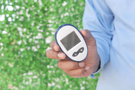 young man holding diabetic measurement tool outdoor with copy space