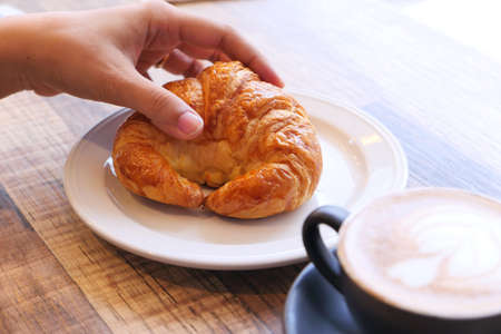 women hand holding croissant on wooden table
