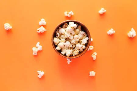 popcorn in a bowl on orange background