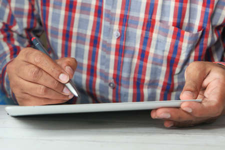 young man with pen using digital tablet on table