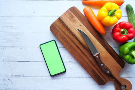 fresh vegetables, cutting board and smart phone on table Stock fotó