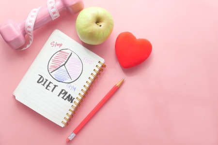 Diet plan with apple and dumbbell on pink background