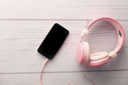 smart phone and headphone on wooden background . Stock fotó