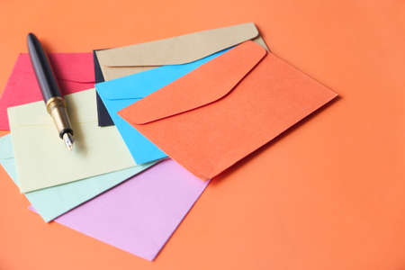 colorful envelopes and fountain pen on orange background