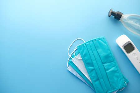 Surgical masks, thermometer and hand sanitizer on orange background