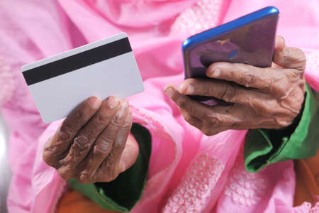 senior women hand holding credit card and using smart phone shopping online 스톡 콘텐츠